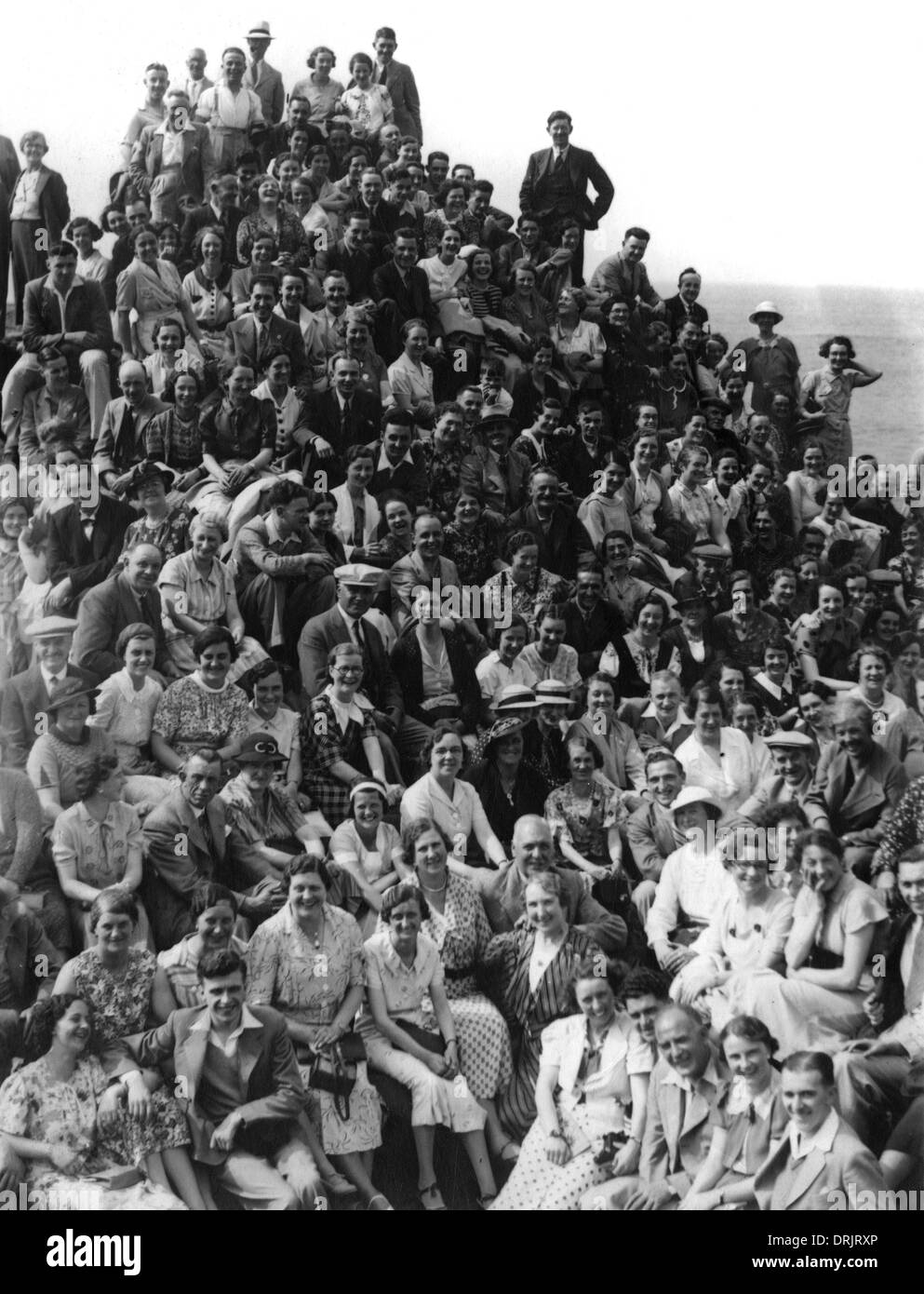 A great crowd of people pose for a photograph by the sea. - Stock Image
