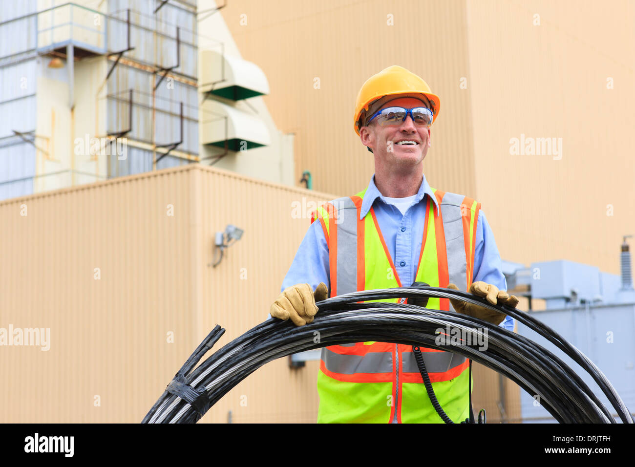 Engineer at electric power plant carrying coil of wire at storage area - Stock Image
