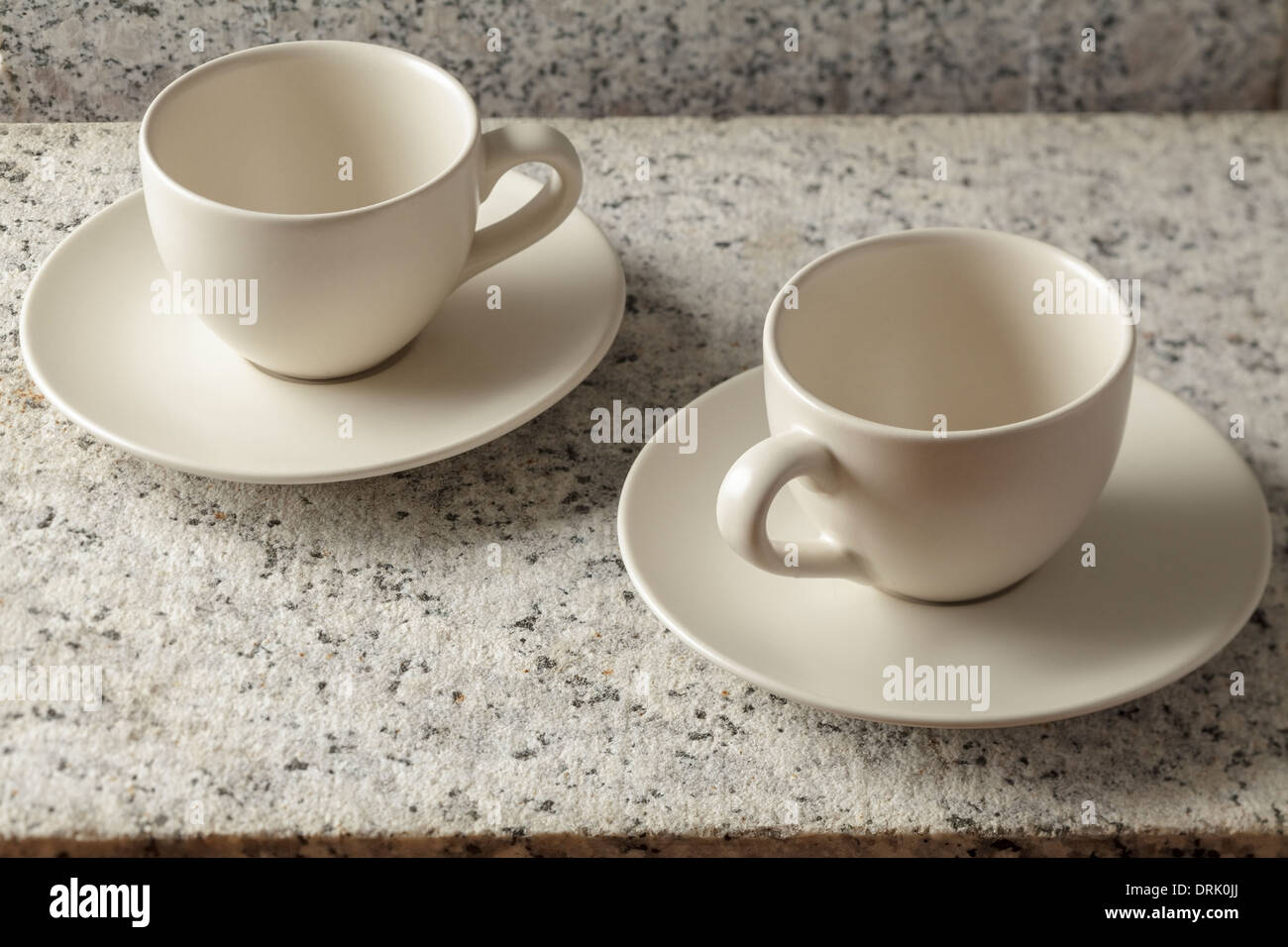 Two coffee cups on rough marble surface - Stock Image