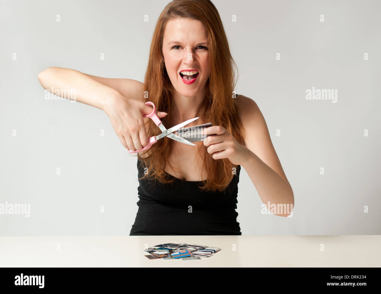 Woman cutting up credit card, a personal financial freedom debt free concept - Stock Image