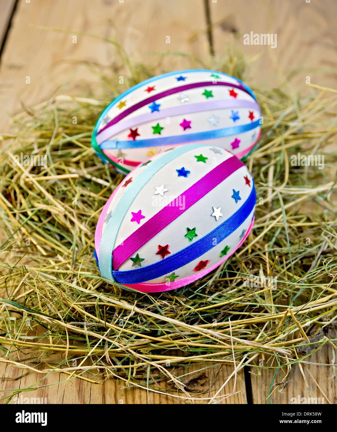 Two easter eggs, decorated with multicolored braid and sparkles as asterisks in the hay on the background of wooden boards - Stock Image