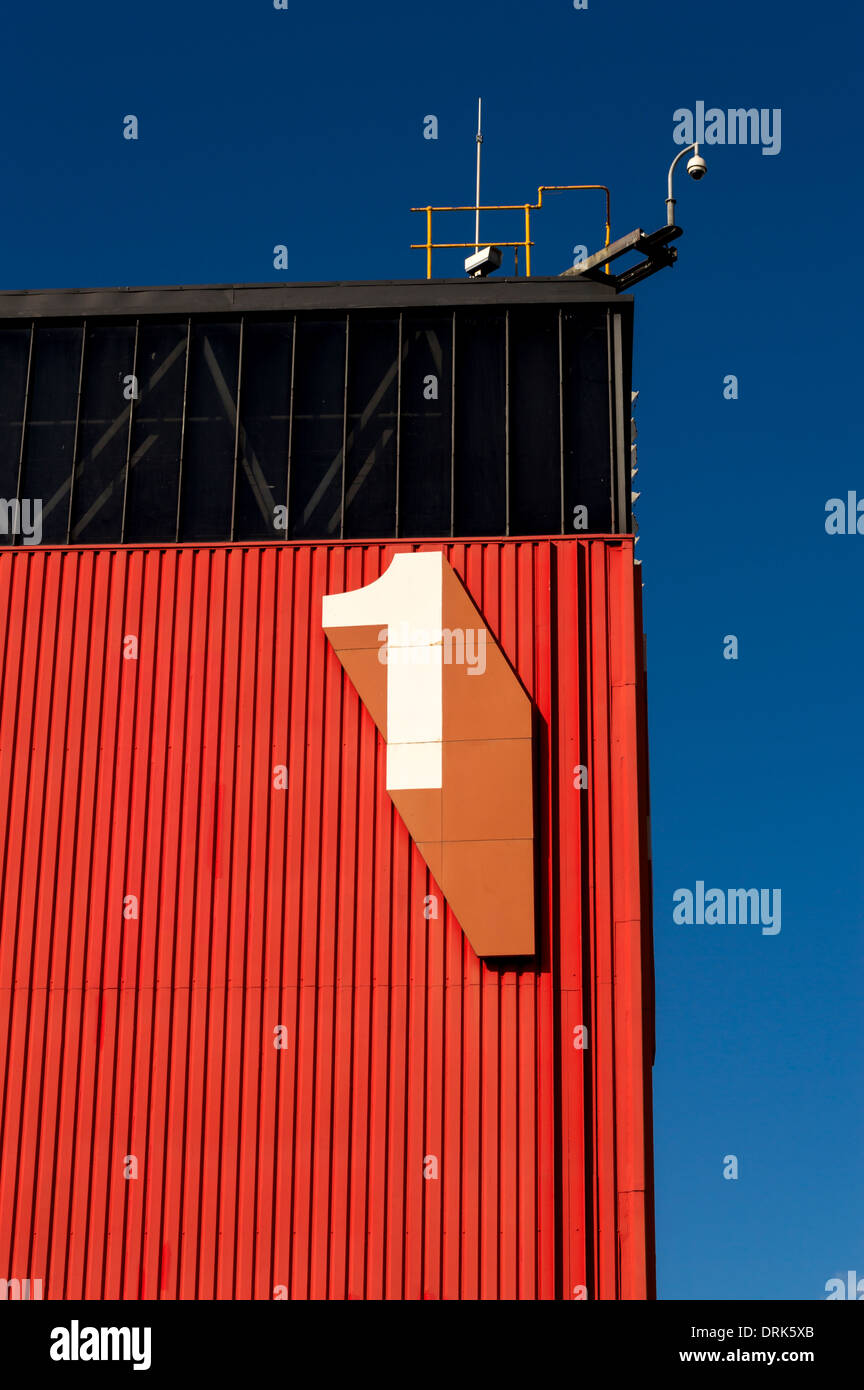 Large number 1 numeral on side of red and black building - Stock Image