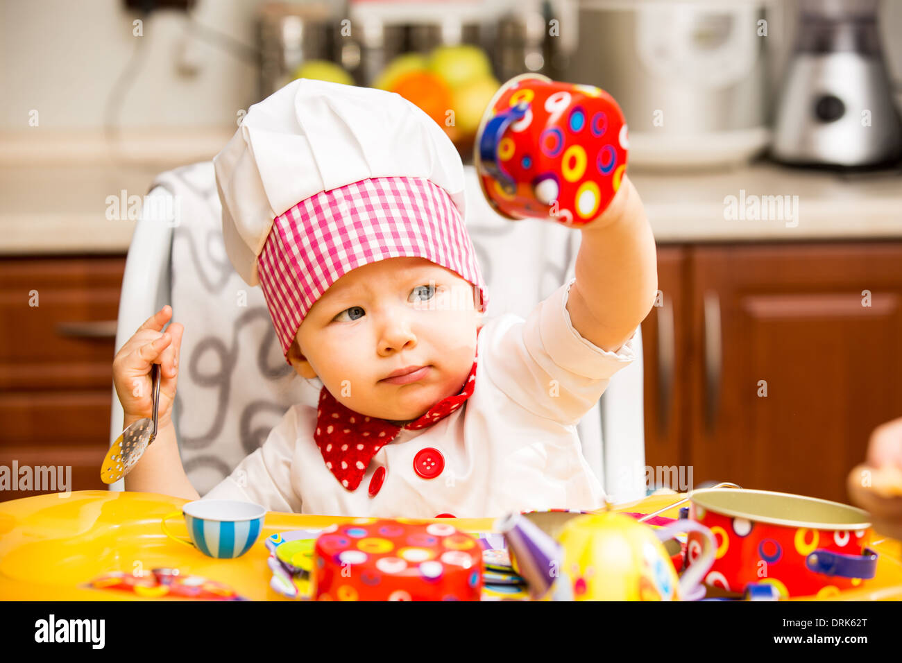 7e24c5fb2fb Baby cook girl wearing chef hat with utensils on kitchen. Use it for a child
