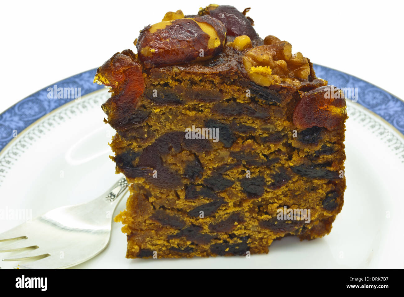 Piece of rich fruit cake on a plate with cake fork. - Stock Image
