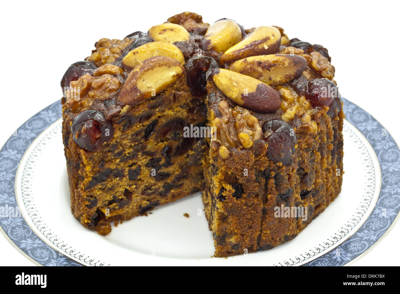 Rich fruit cake decorated with glace  cherries and nuts. - Stock Image