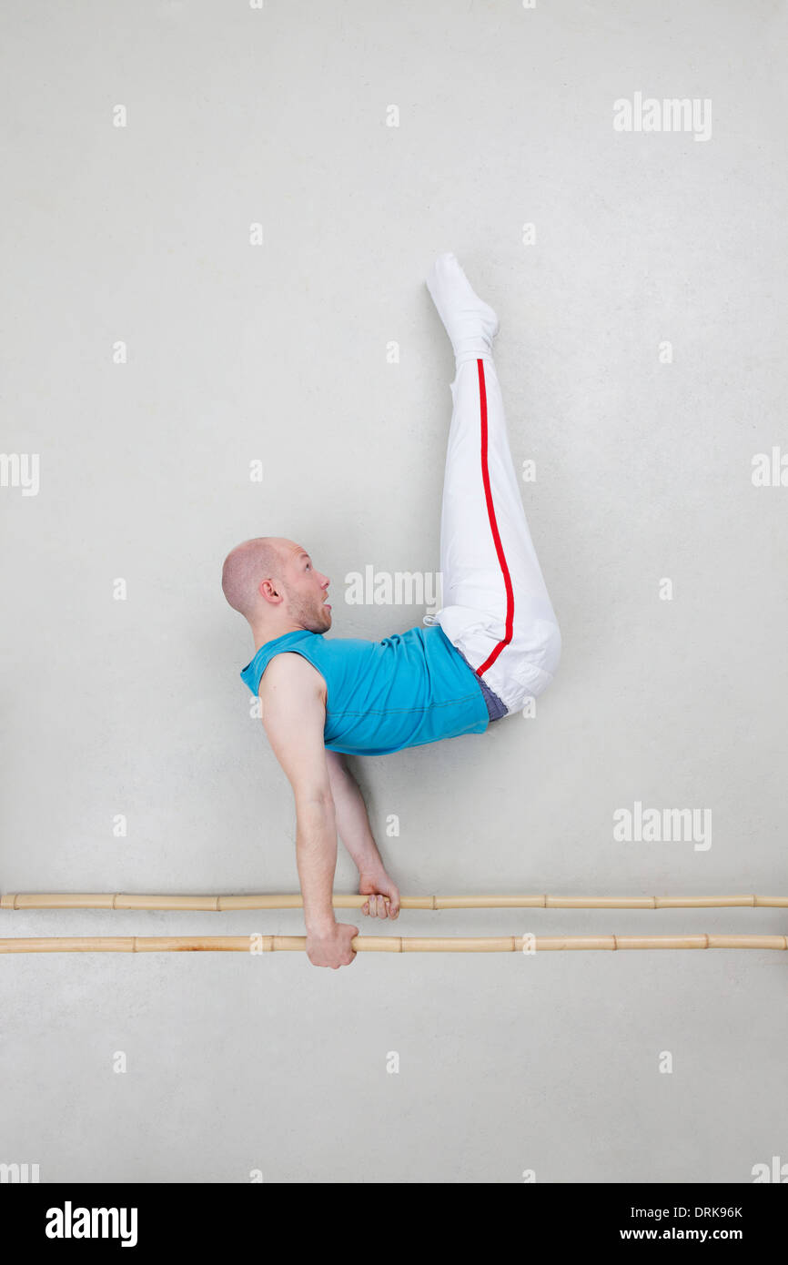 Man exercising on parallel bars - Stock Image