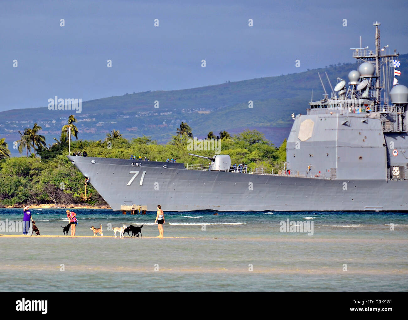 US Navy guided missile cruiser USS Cape St George transits the waters of Pearl Harbor past bathers January 25, 2014 in Honolulu, HI. - Stock Image