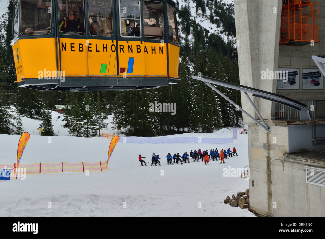 Nebelhorn cablecar docking at 1st of the 2 transfer stations to Nebelhorn's summit (2.224m).Skiers about to descend on ski bikes - Stock Image