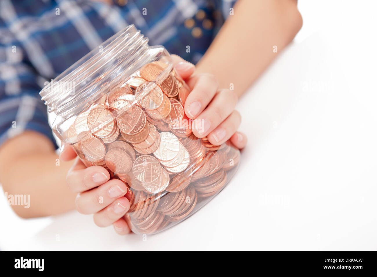 Young woman/girl with her hands holding a large savings jar full of British copper coins. - Stock Image