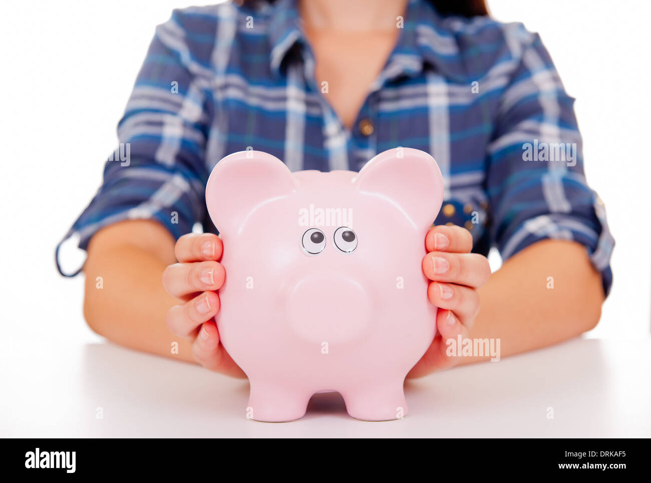 Young girl/woman with her hands holding onto a large pink piggy bank. - Stock Image