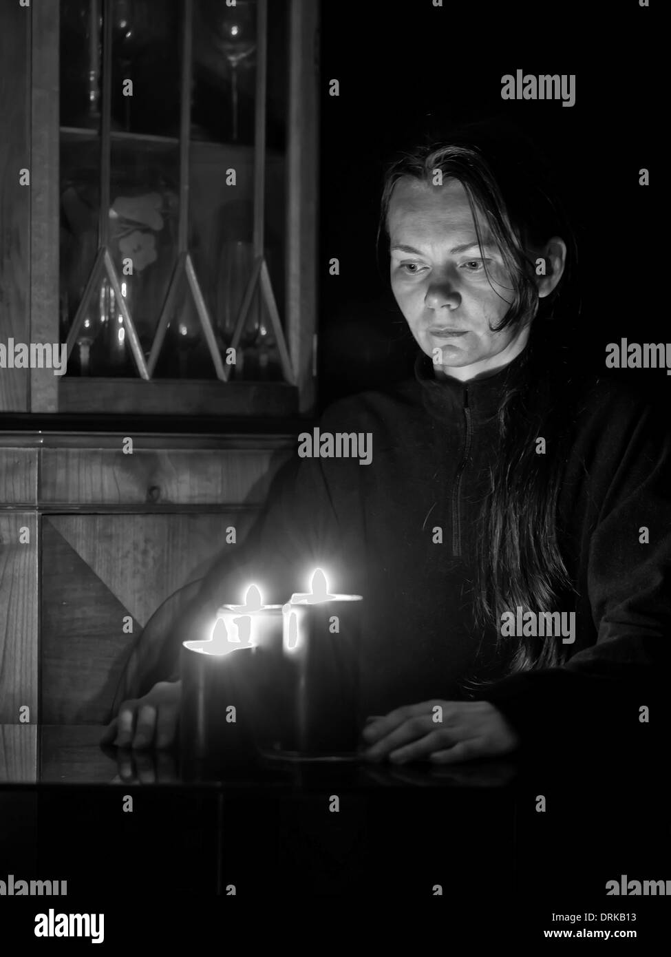 A black and white image of a female fortune teller looking into candles - Stock Image