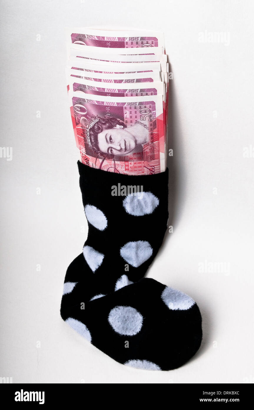 Fifty pound banknotes stuffed in a sock - Stock Image