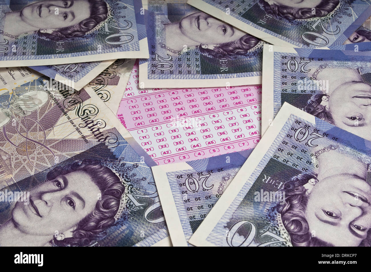 Blank lottery ticket in the middle of a pile of scattered twenty pound notes Stock Photo