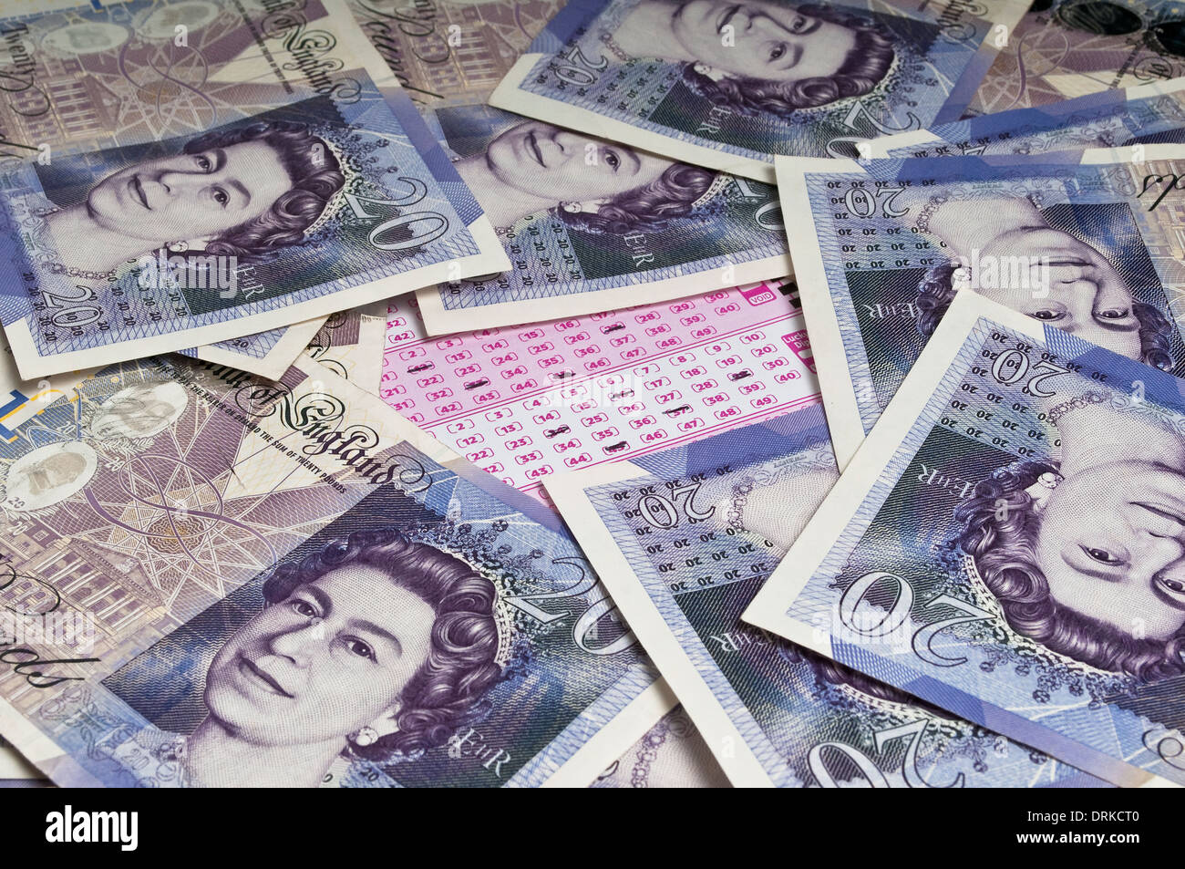 Marked lottery ticket in the middle of a pile of scattered twenty pound notes Stock Photo