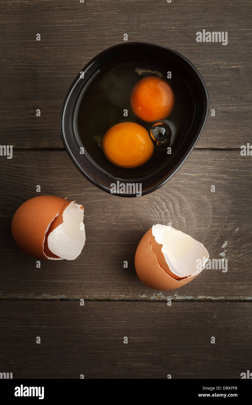 Bowl of two breaked open eggs and egg shells on wooden table, studio shot - Stock Image