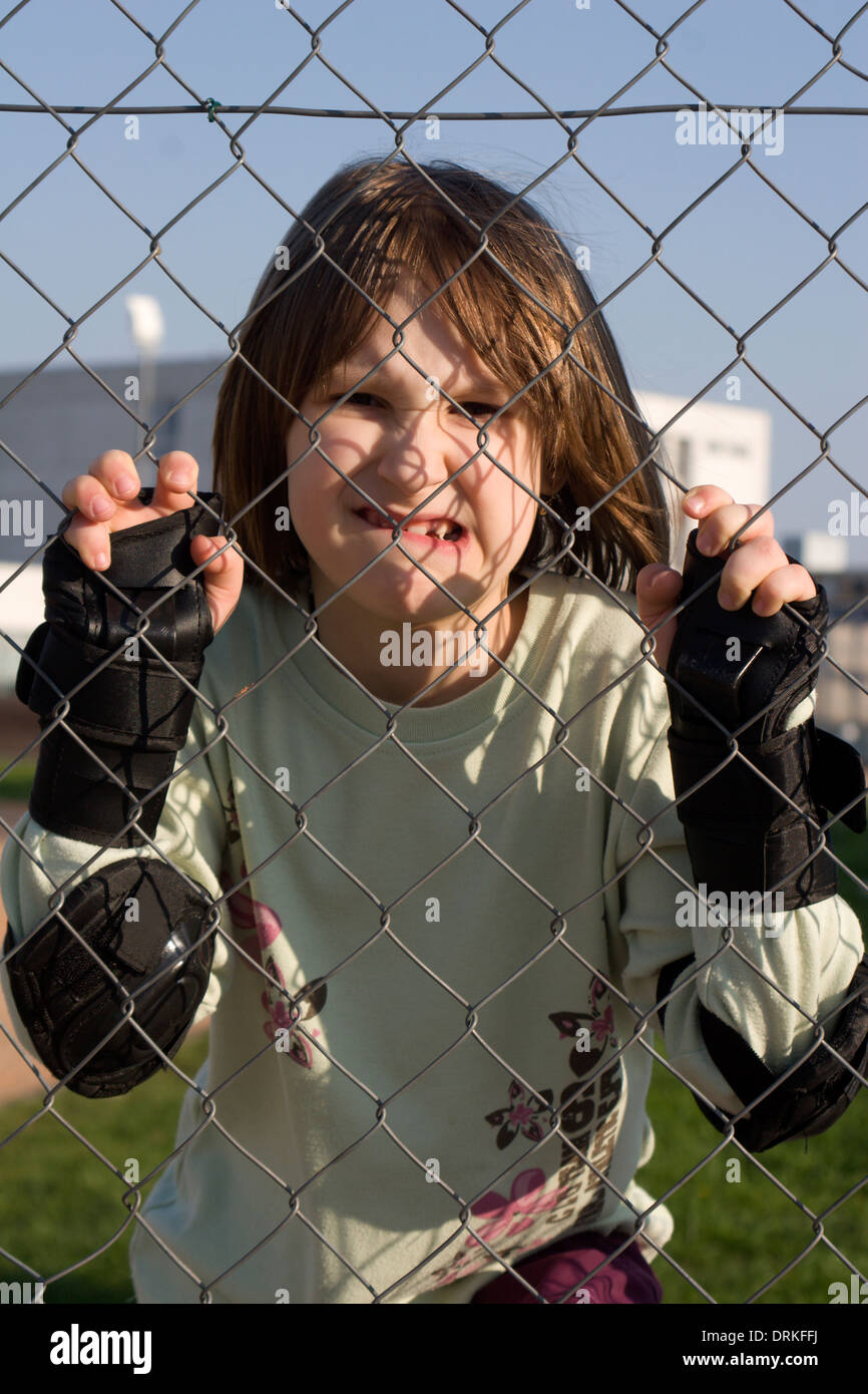 portrait of little girl and fence Stock Photo