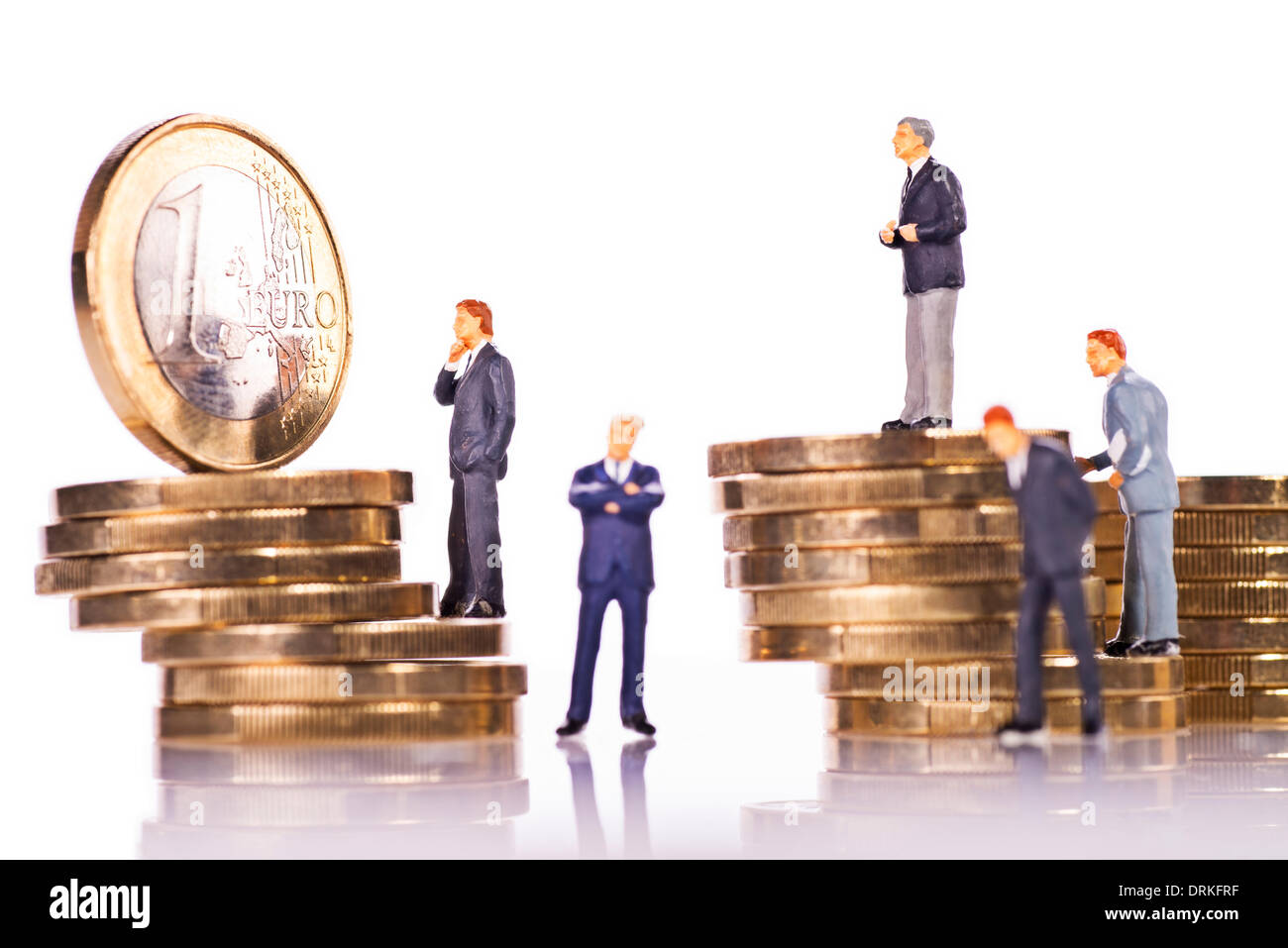 Model figures of business people with euro coins. - Stock Image