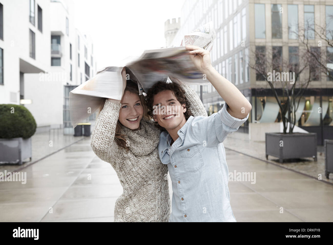 Young couple on the move in the rain - Stock Image