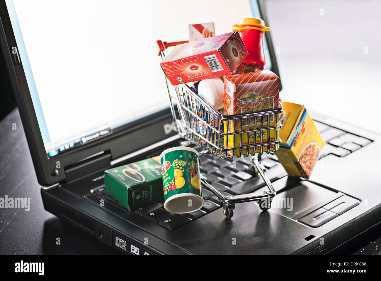 Miniature shopping cart with food packaging and laptop as a symbol for online shopping. Stock Photo