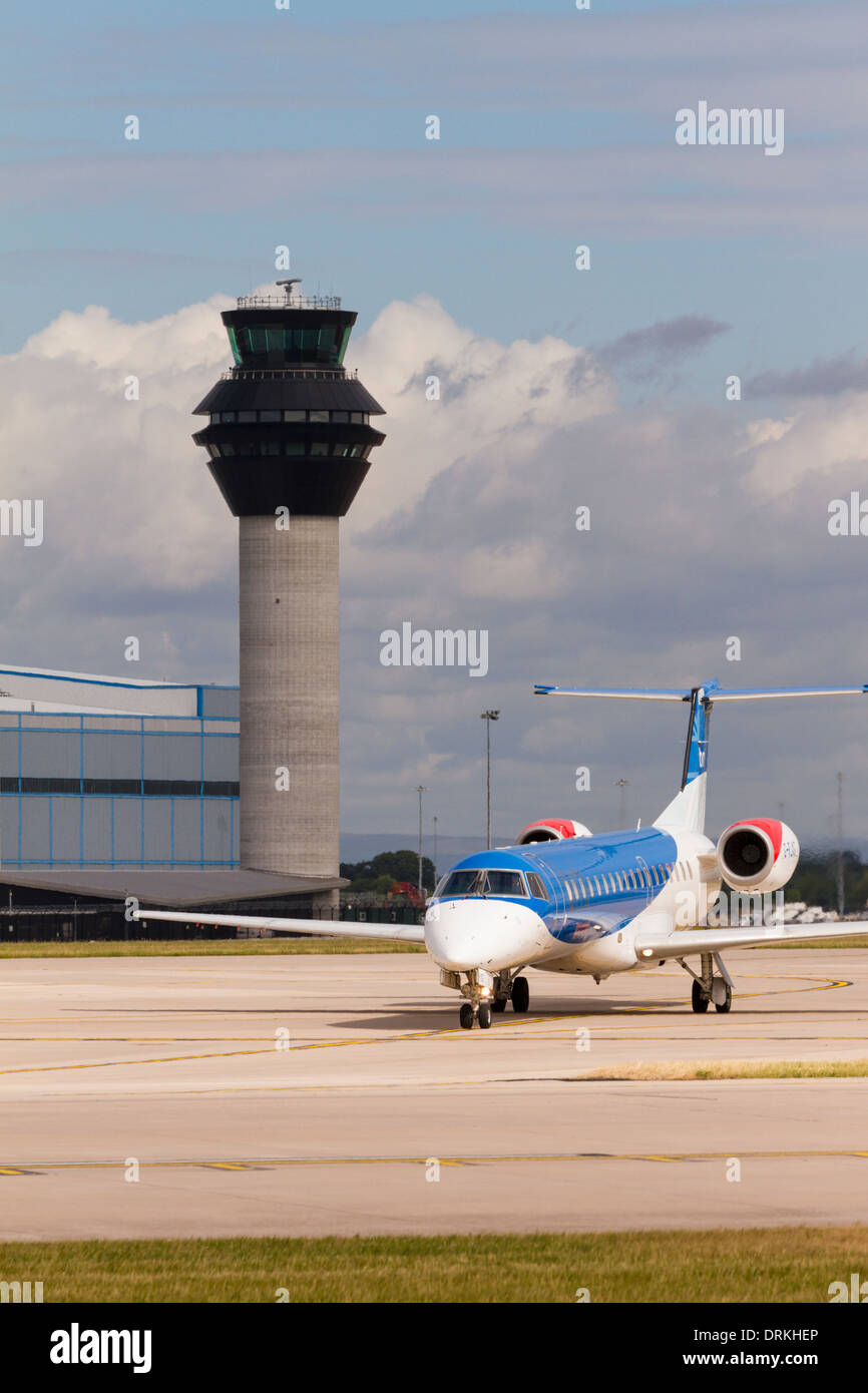 BMI Embraer taxis past control tower for take off at Manchester Airport - Stock Image