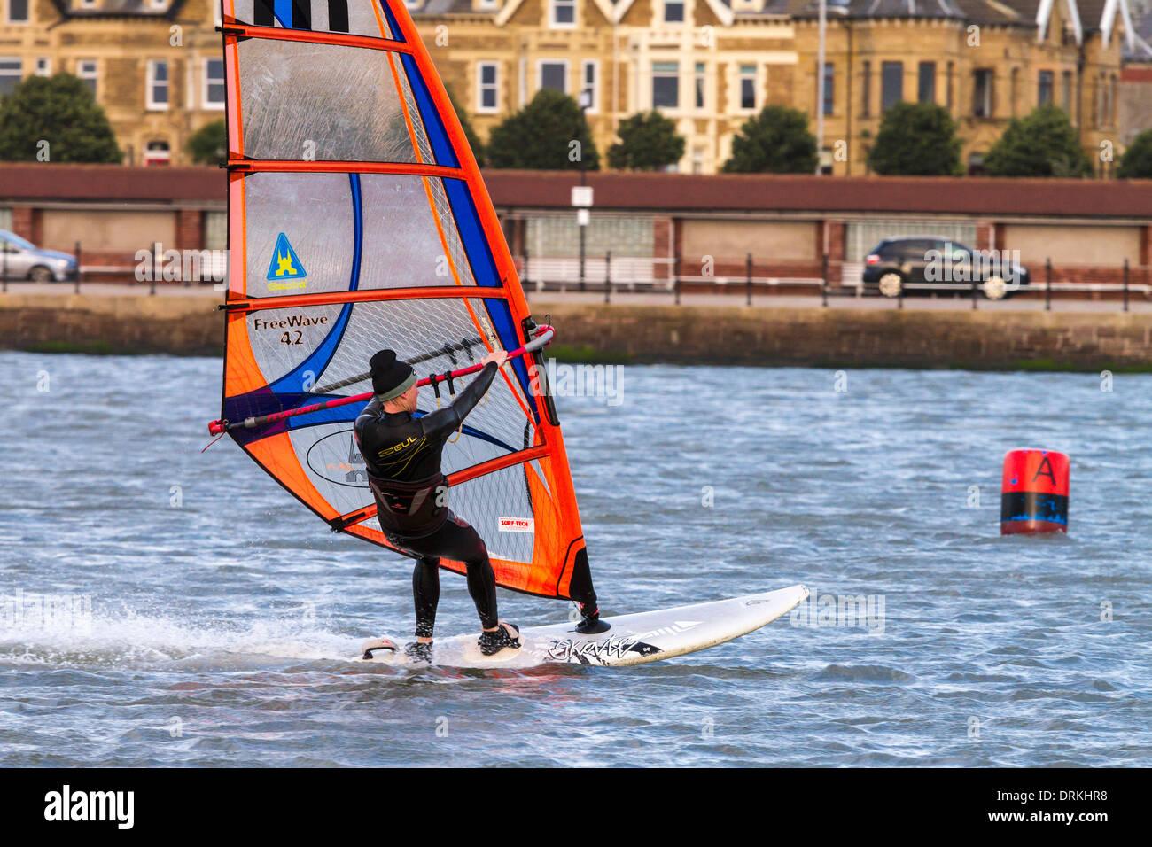 Male windsurfer sails on marine lake - Stock Image
