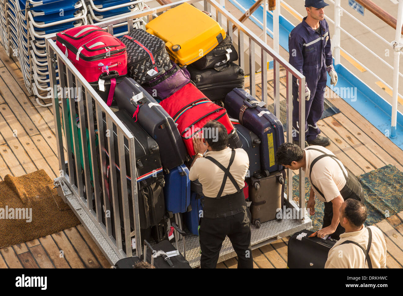 Men loading baggage crate for offloading from cruise ship - Stock Image