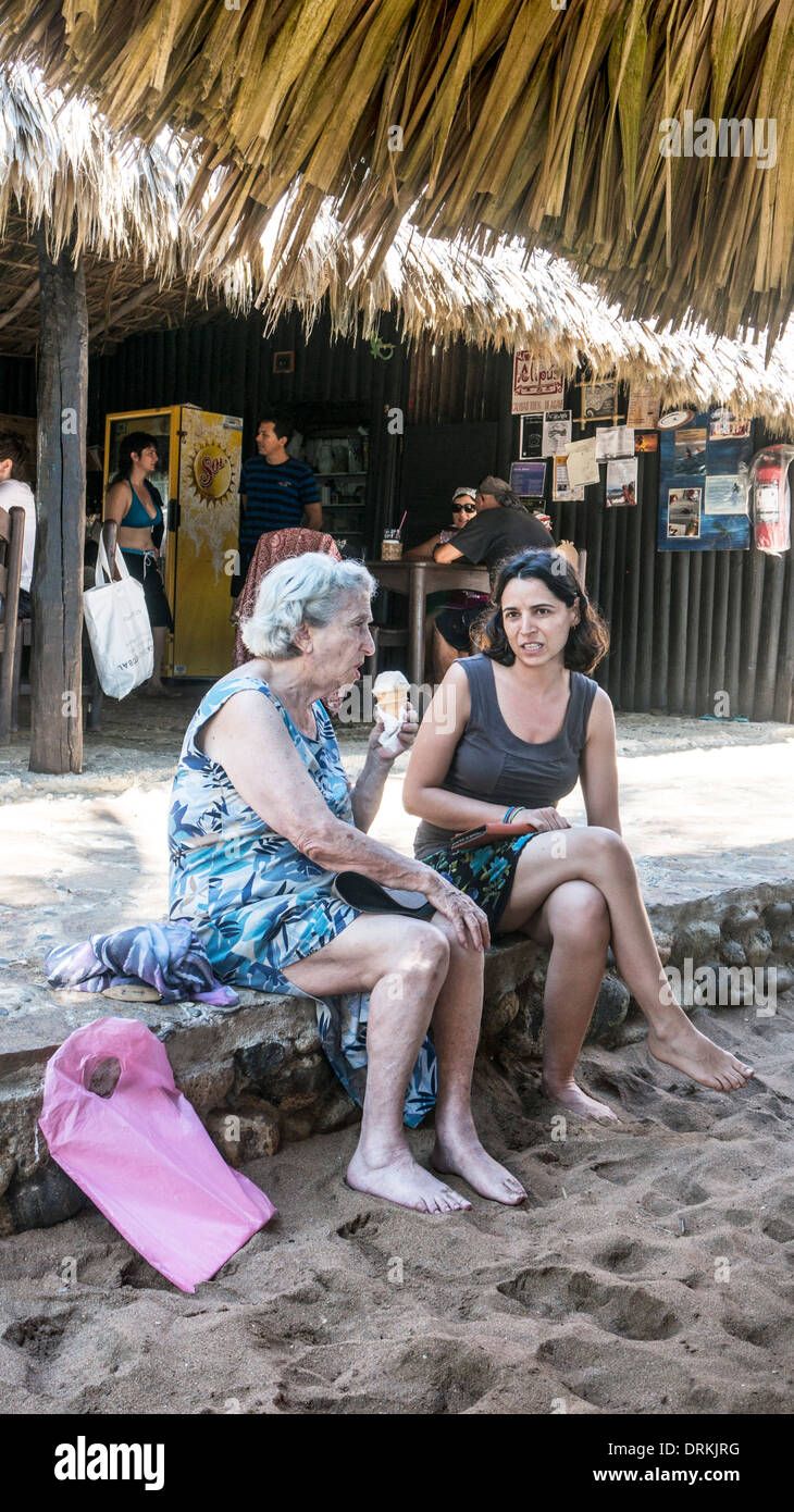old woman eating ice cream & gossiping with young woman relative sitting on curb of terrace at popular beachfront Stock Photo