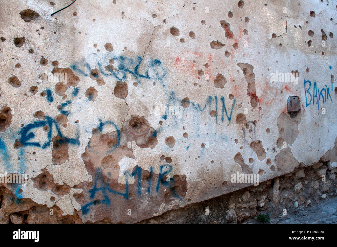A wall riddled by bullets with graffiti, Mostar, Bosnia and Herzegovina - Stock Image