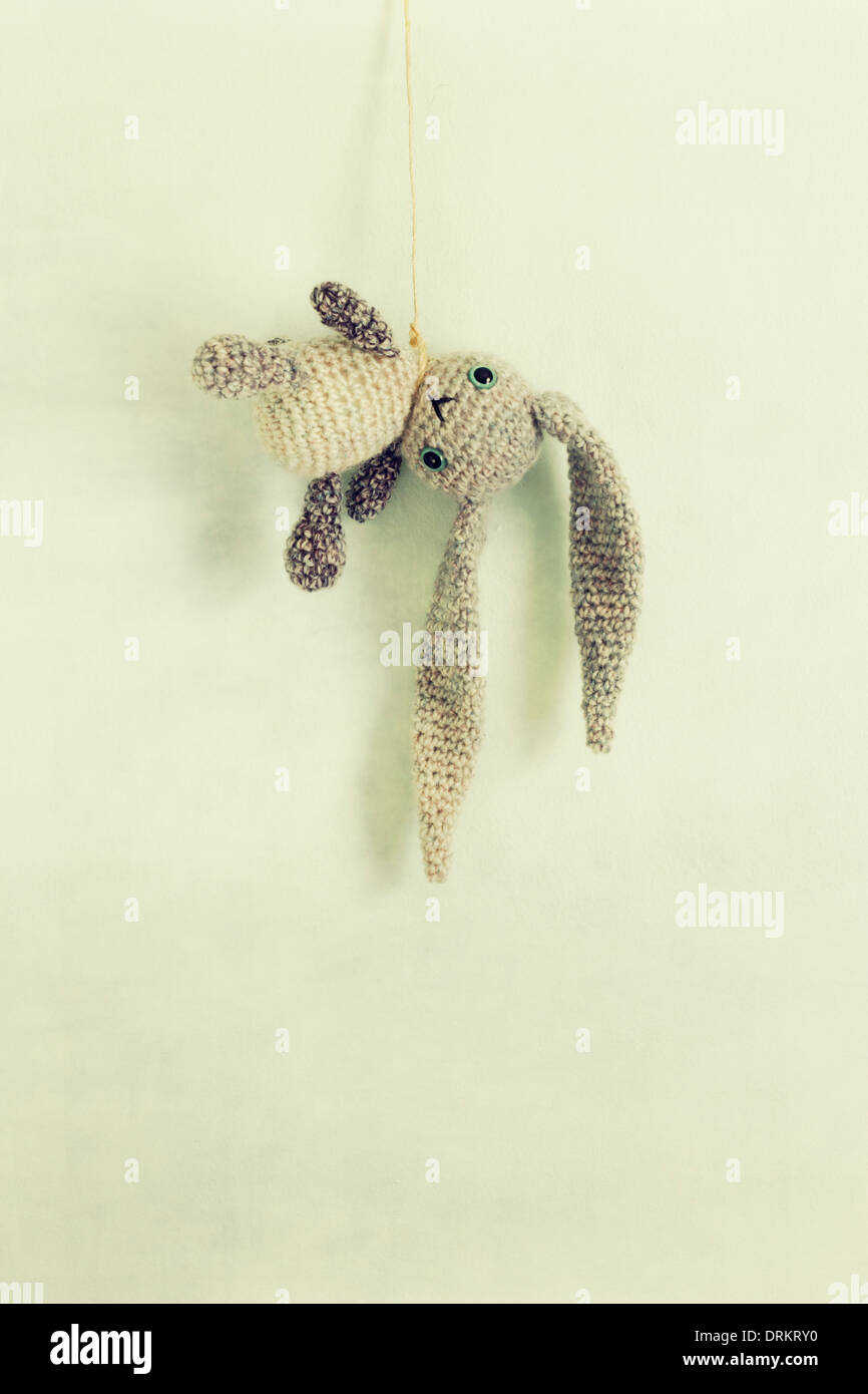 A crocheted toy bunny with long floppy ears hangs from a string/noose. - Stock Image