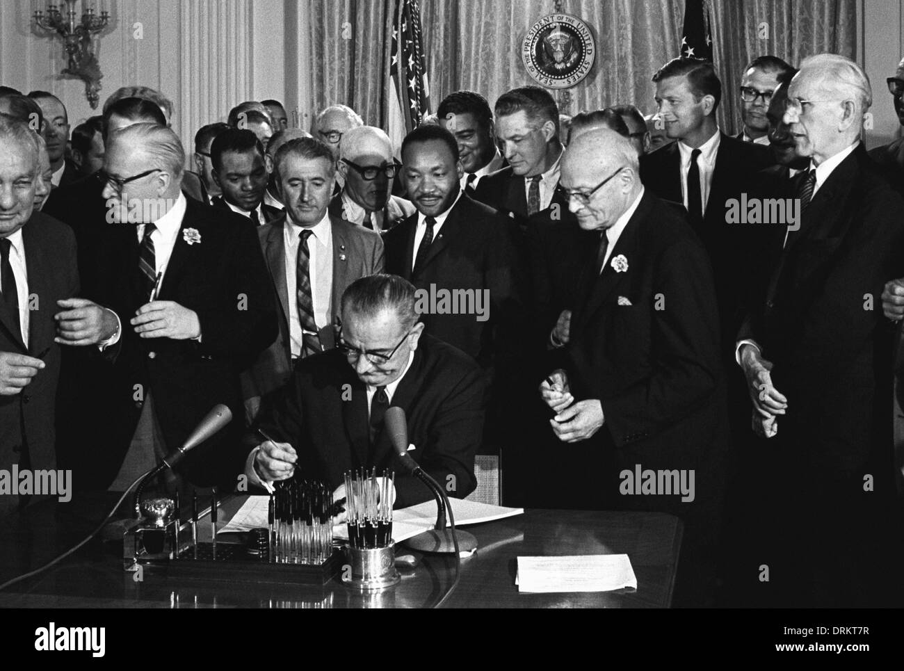 US President Lyndon B. Johnson signs the 1964 Civil Rights Act as Martin Luther King, Jr., others look on in the East Room of the White House July 2, 1964 in Washington, DC. - Stock Image