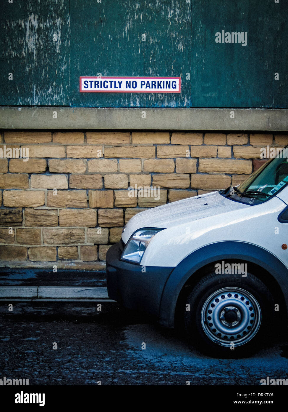 Vehicle parked in front of Strictly No Parking sign - Stock Image