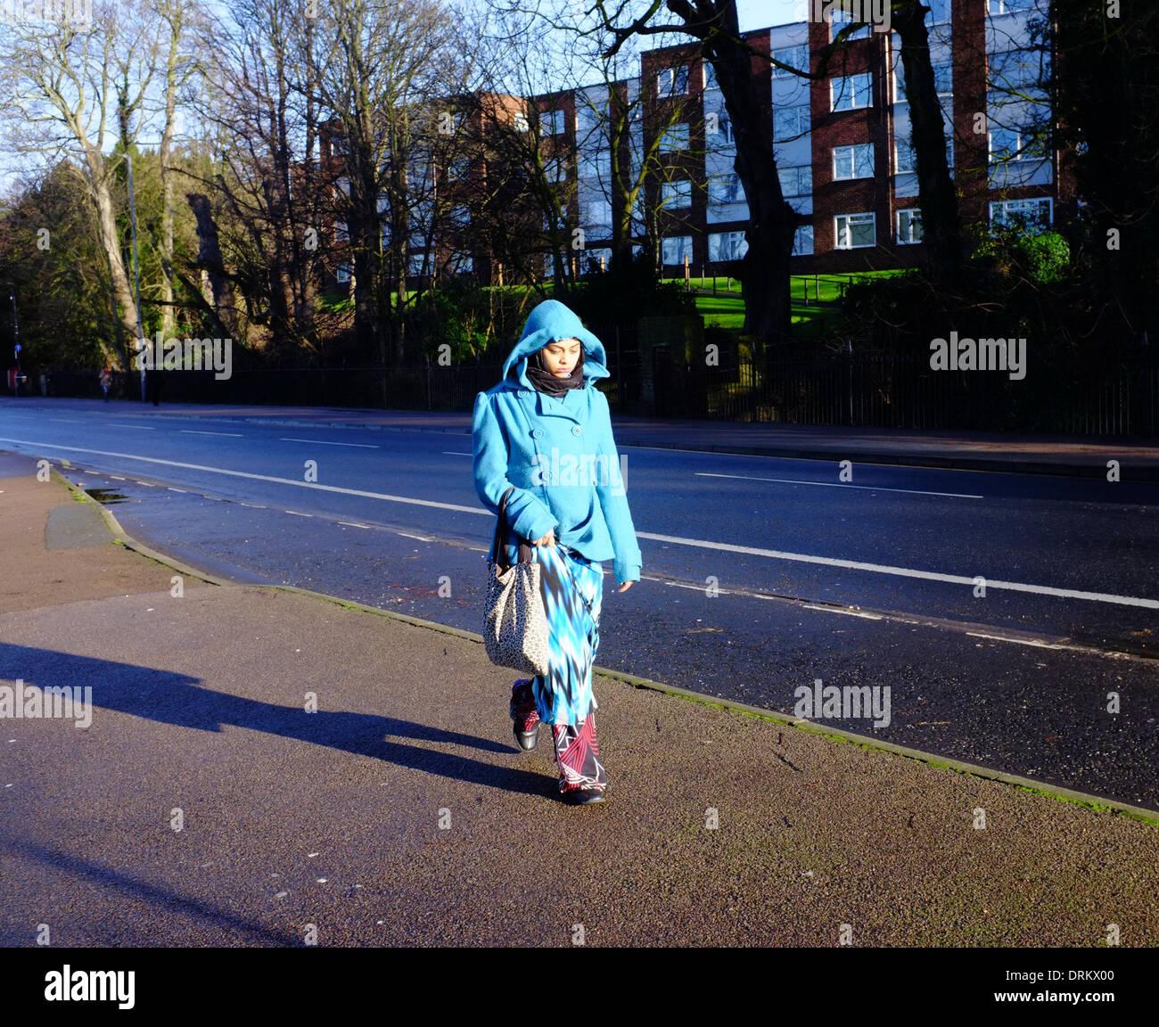Asian woman in blue hooded coat walking in Luton - Stock Image