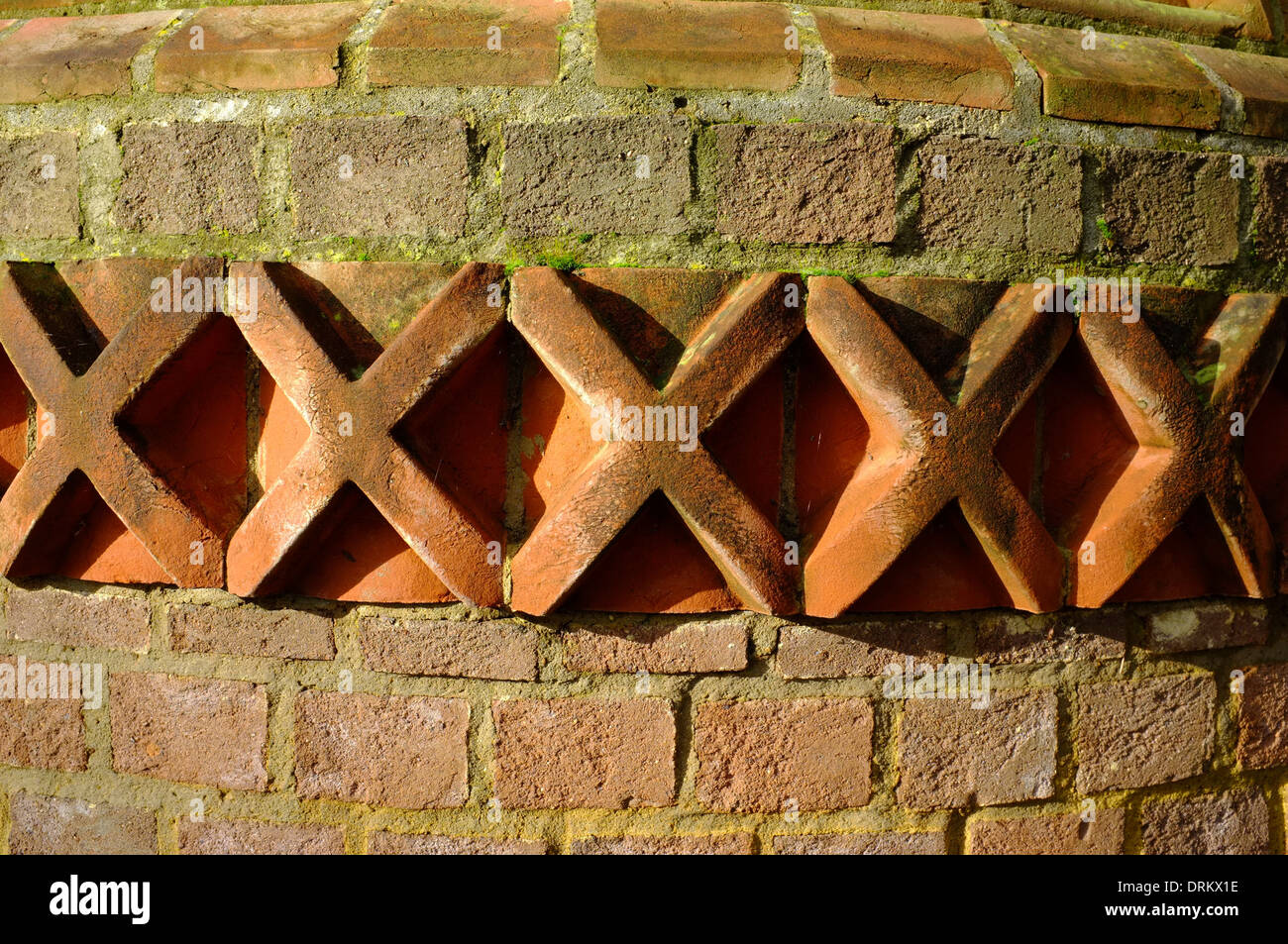 Terracotta decorative tiles within a brick wall in Wardown Park, Luton - Stock Image