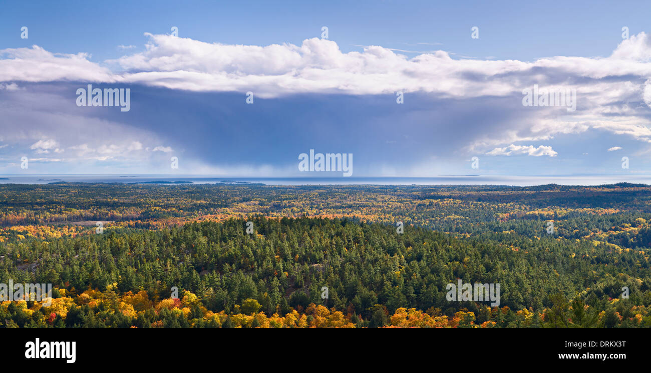 A storm cloud receding over an expansive view of fall foliage in Killarney Provincial Park, Ontario, Canada. - Stock Image