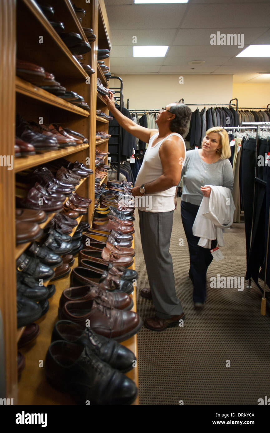 An unemployed Hispanic man proudly gets new business clothing from an organization helping the unemployed dress for success - Stock Image