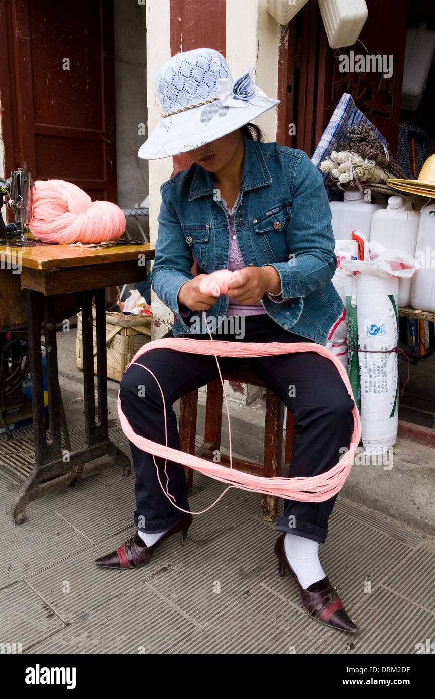 Young woman / girl winding skein / skeins / ball / balls of wool in Songpan, northwestern Sichuan province, China. - Stock Image
