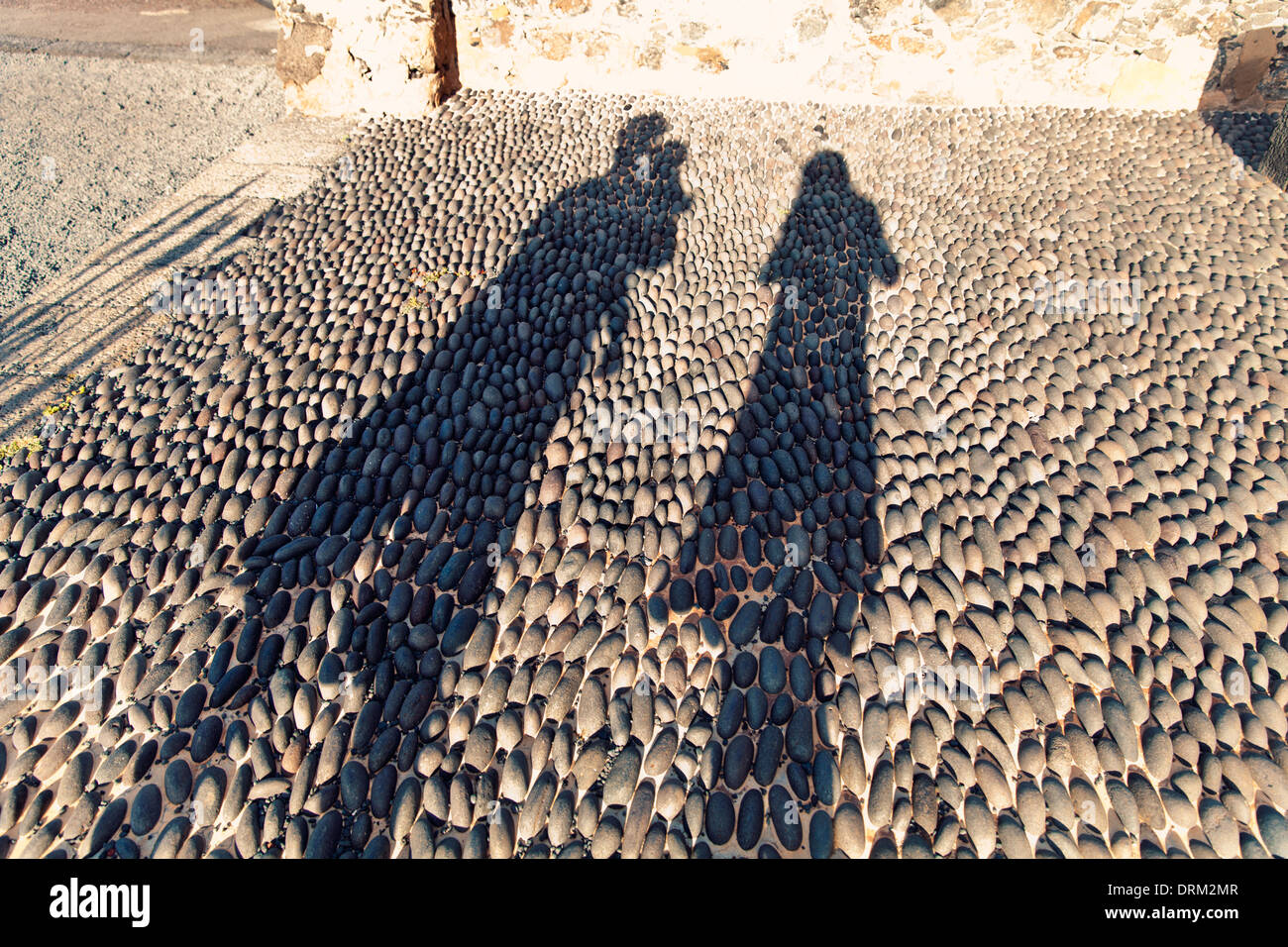 Spain, Lanzarote, Arrecife, silhouettes of family on pavement - Stock Image