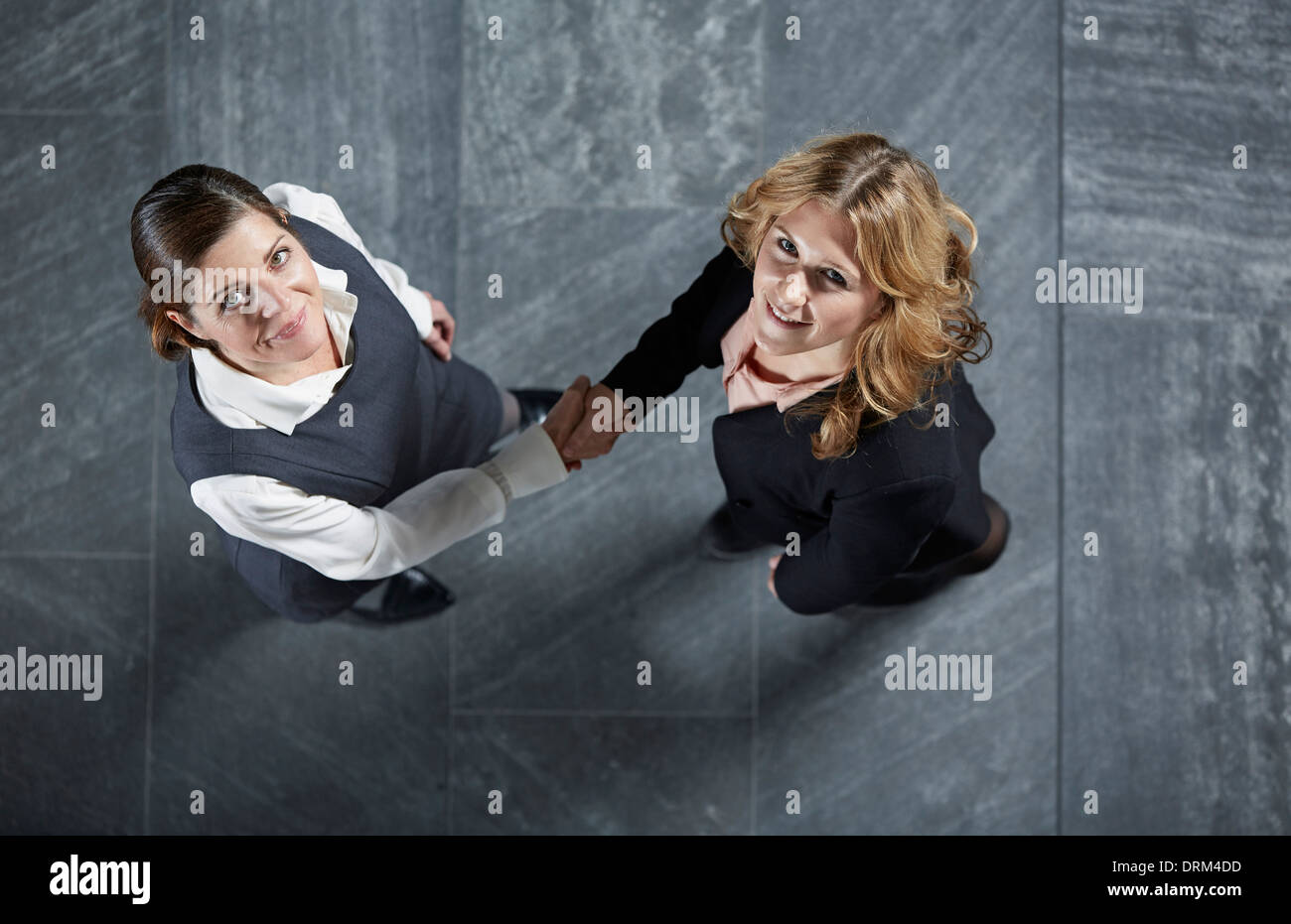Germany, Neuss, Business women shaking hands, looking up to camera - Stock Image