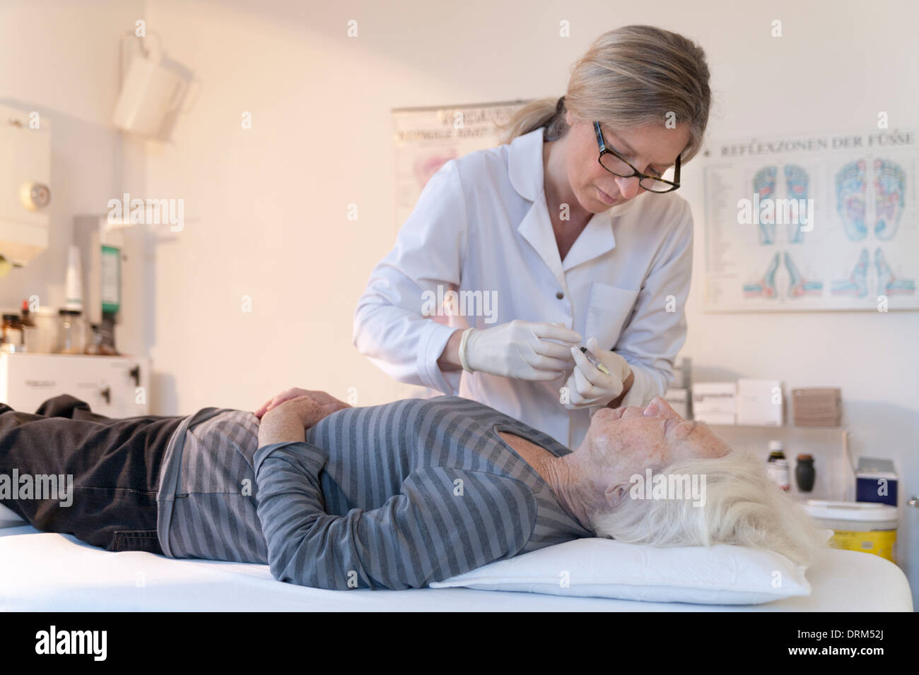 Female alternative practitioner giving senior woman injection acupuncture - Stock Image