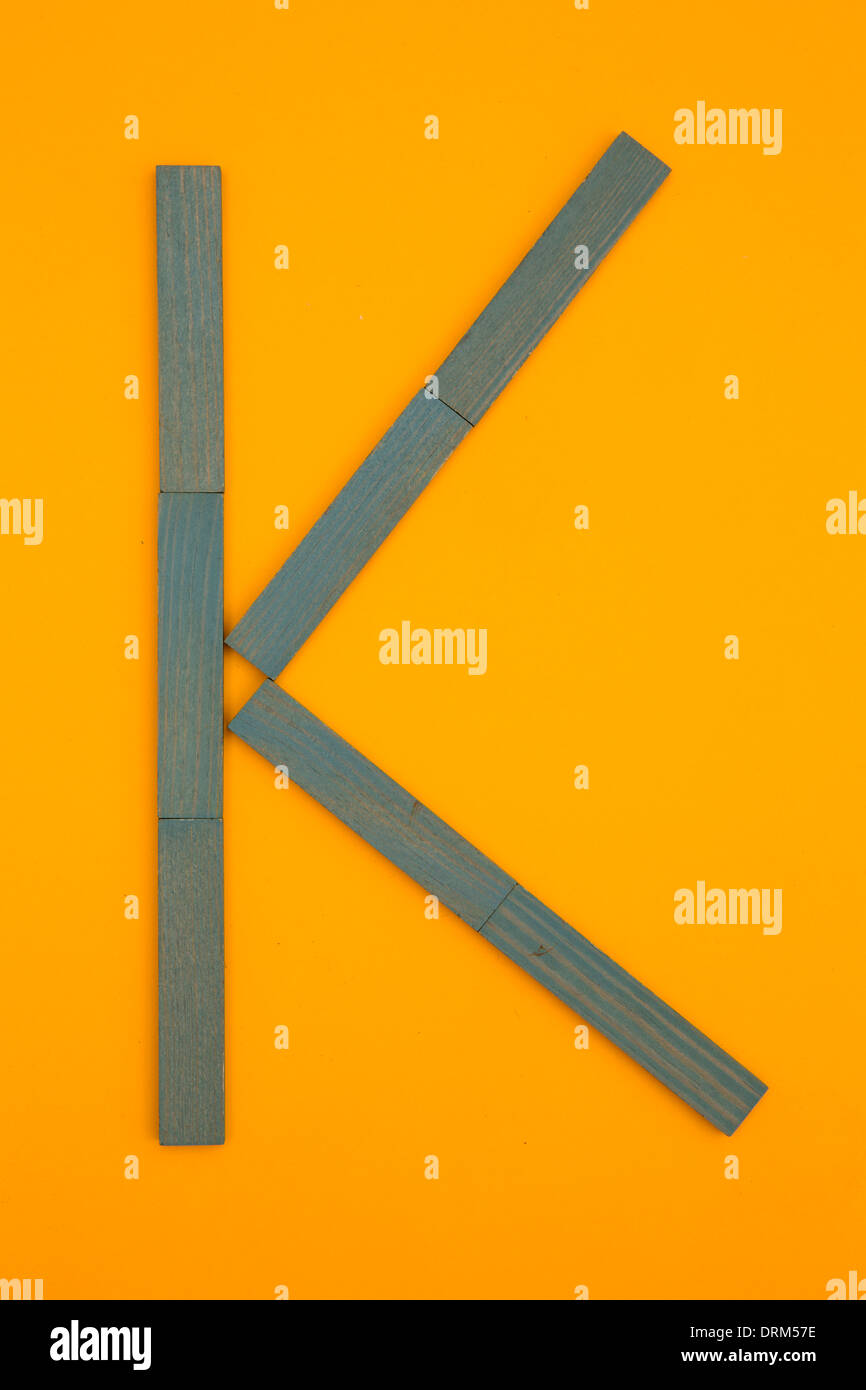 Letter 'K' formed of blue building bricks at yellow background, studio shot - Stock Image