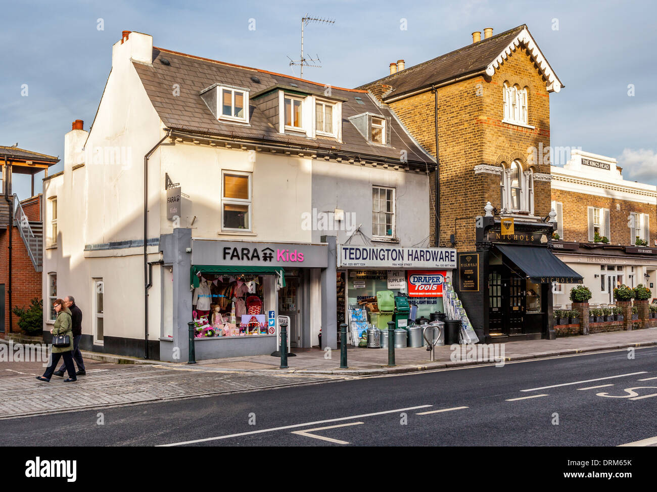 High street shops - Fara Kids, Hardware store, Nichols Jeweller and the King's Head pub in Teddington, Greater London, Uk - Stock Image