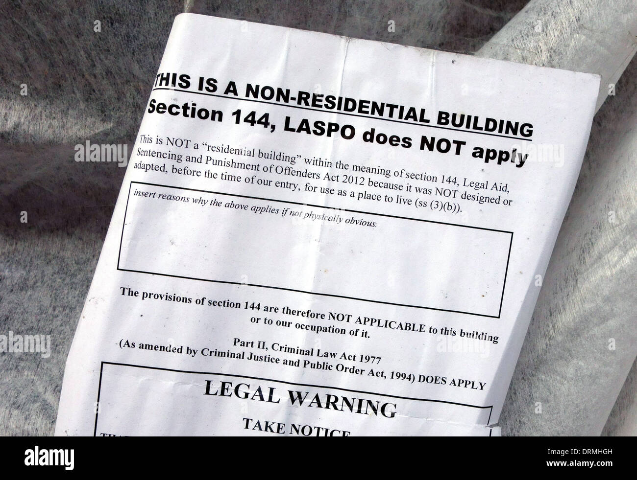 Legal notice in window of squat in non-residential building, London: anti-squatting law does not apply to commercial premises - Stock Image