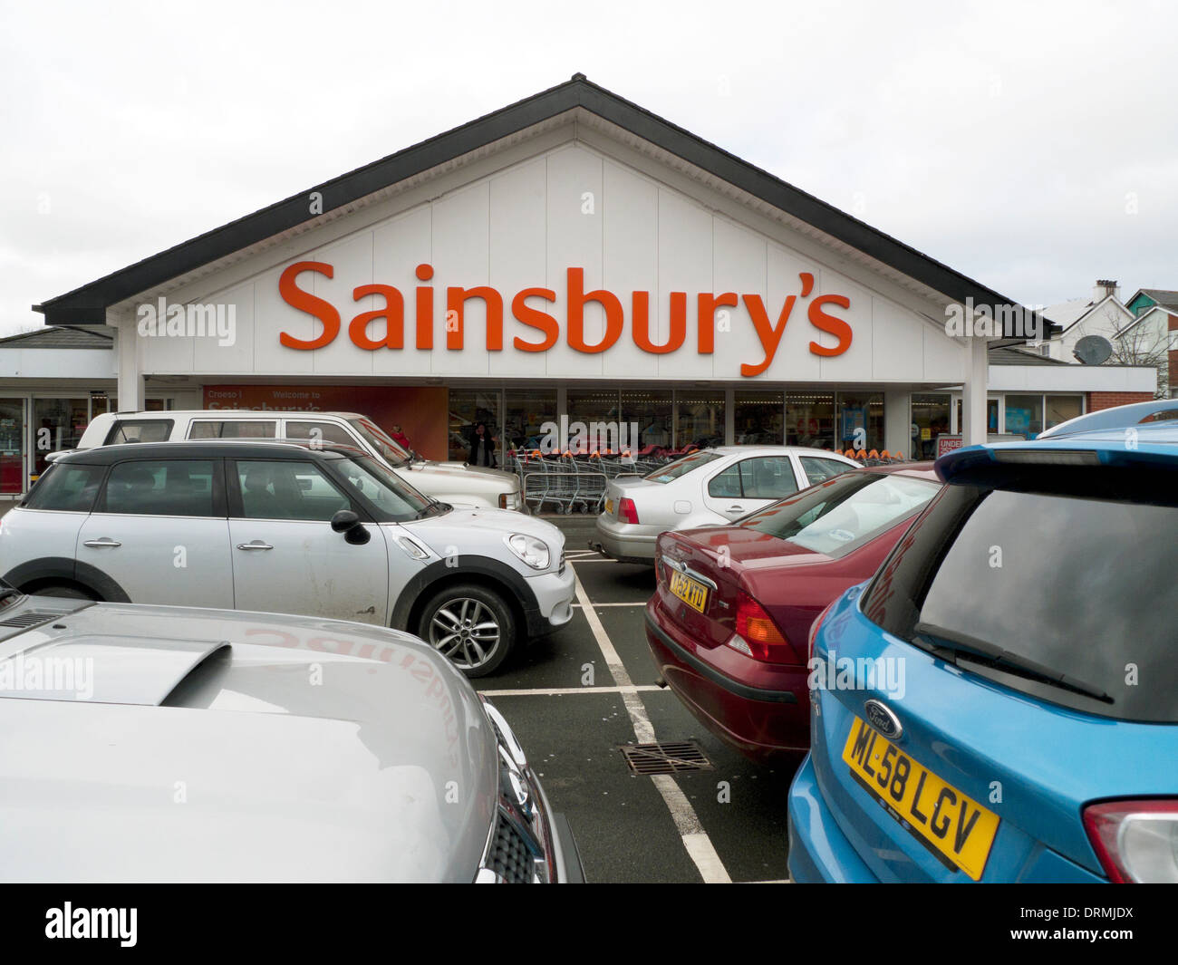 Exterior view of Sainsbury's supermarket sign and cars in car park parking lot Lampeter Wales UK  KATHY DEWITT - Stock Image