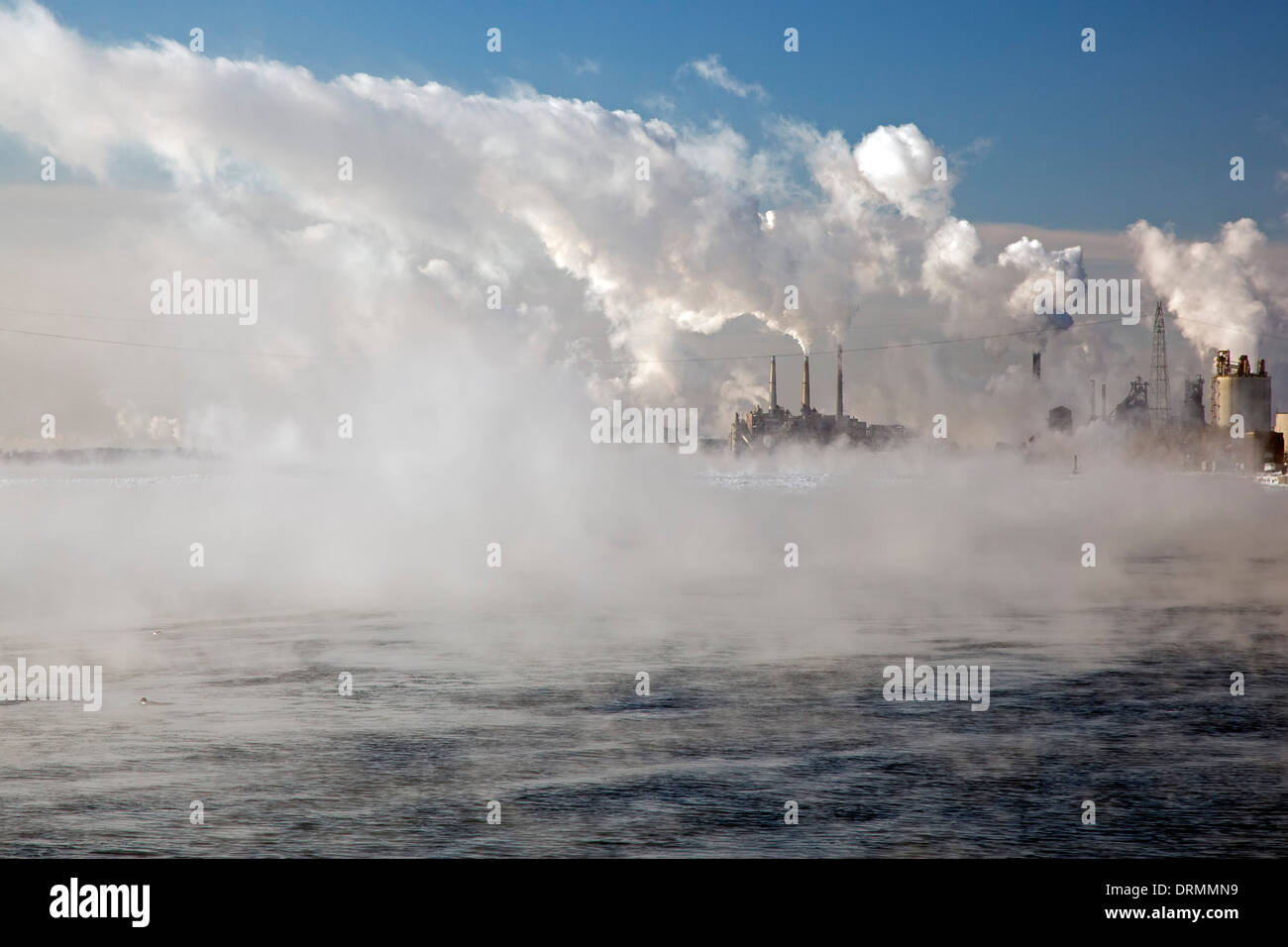 Detroit, Michigan - Smoke from industry mixes with water vapor from the Detroit River on a below zero morning. - Stock Image