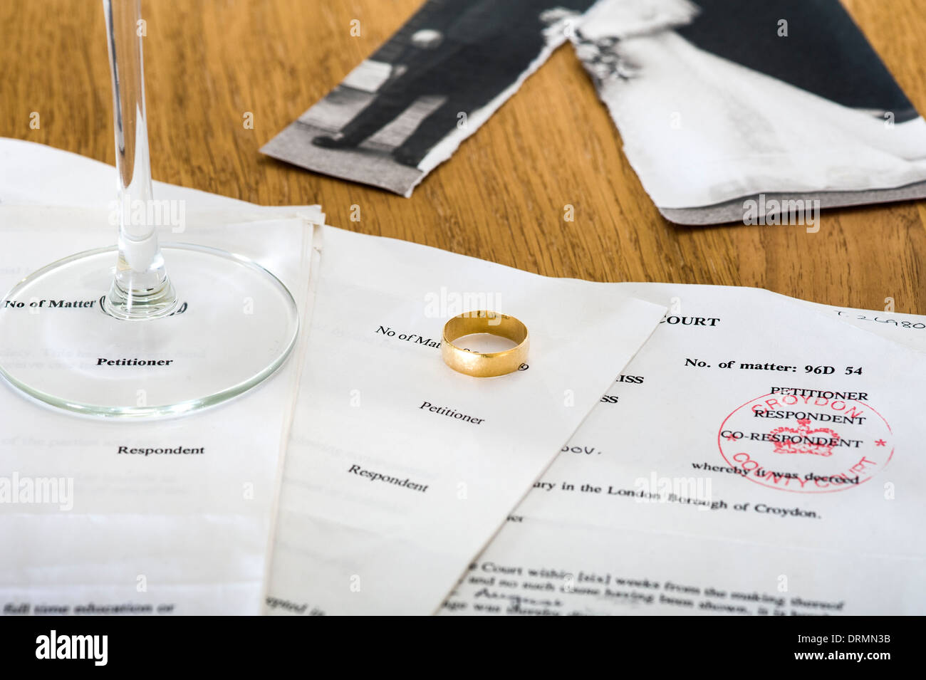 Divorce documents on a table, with wedding ring and wedding photograph. - Stock Image