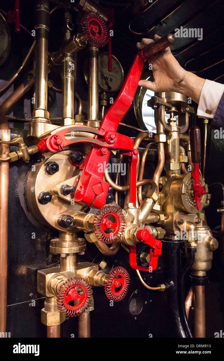 Fabricated model with hand on regulator on steam locomotive footplate - Stock Image