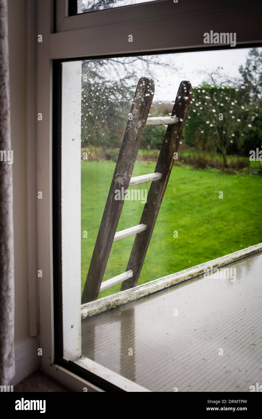 A maintenance ladder left giving access to roof and presenting a security risk of uninvited intrusion - Stock Image