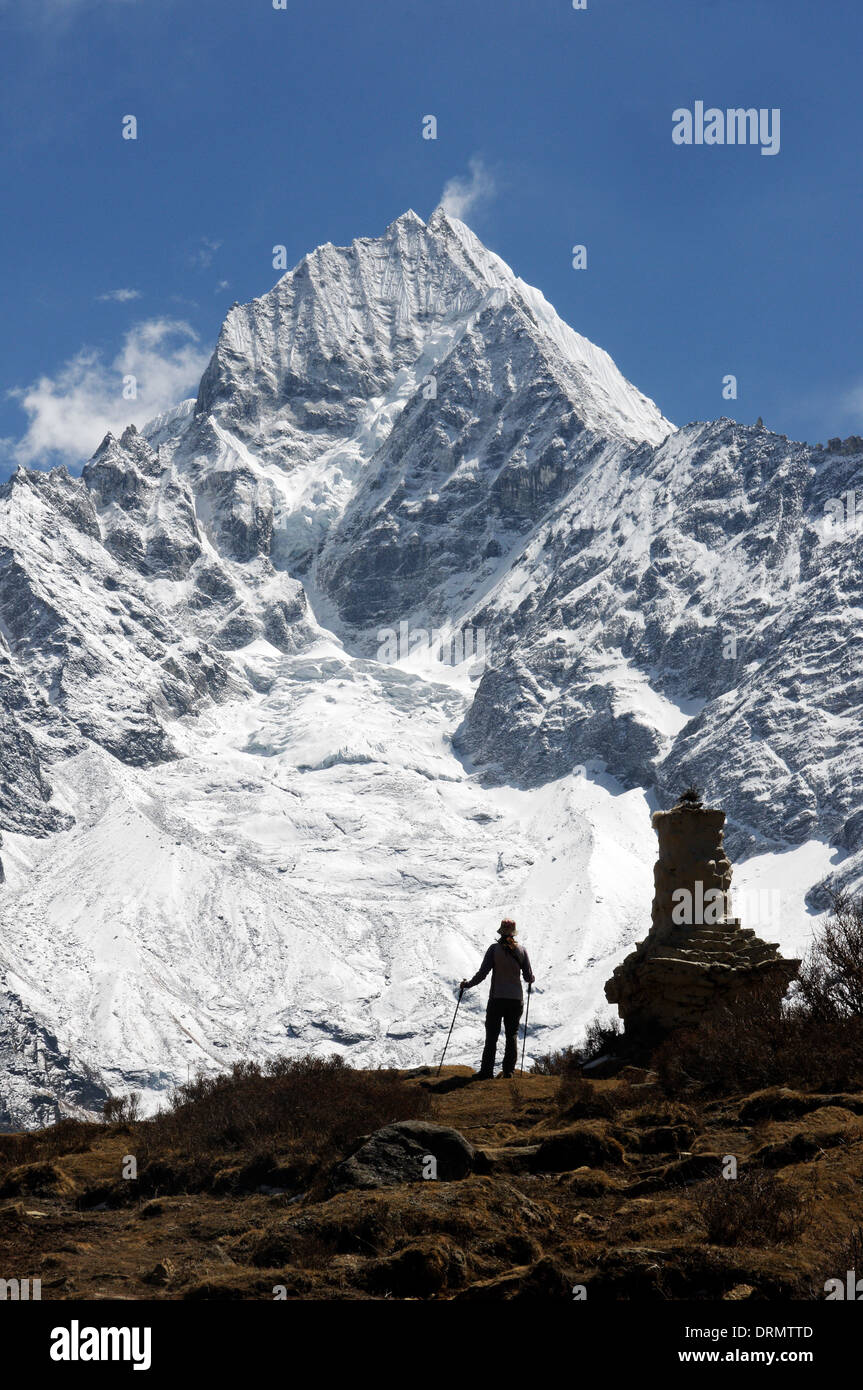 A trekker in silhouette against Thamserku near Khumjung on the Everest Base Camp trek - Stock Image