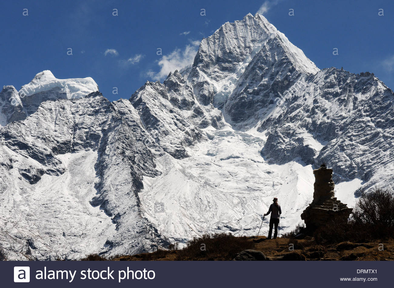 A trekker in silhouette against Thamserku near Khumjung on the Everest Base Camp trek - Stock Image