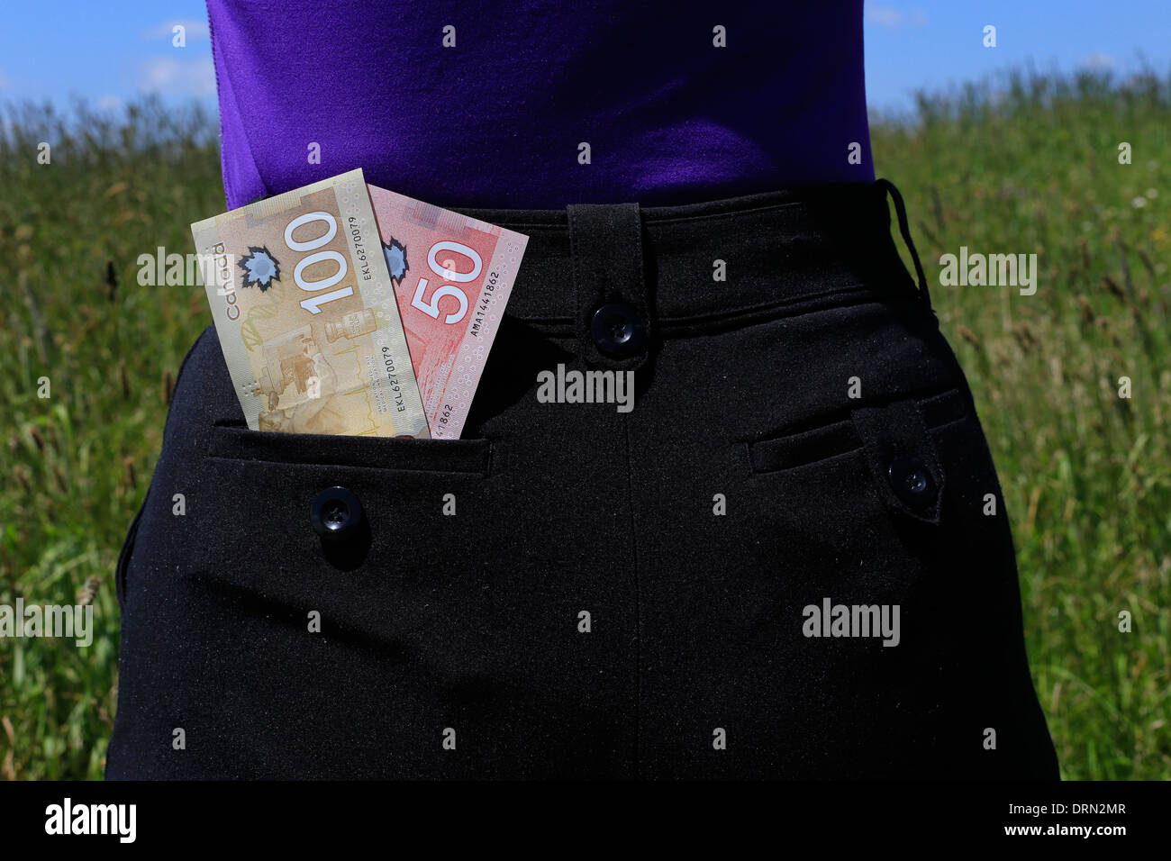 A 100 Canadian dollar bill and a 50 Canadian dollar bill tucked in the back pocket of a woman's pants who is standing in a field - Stock Image